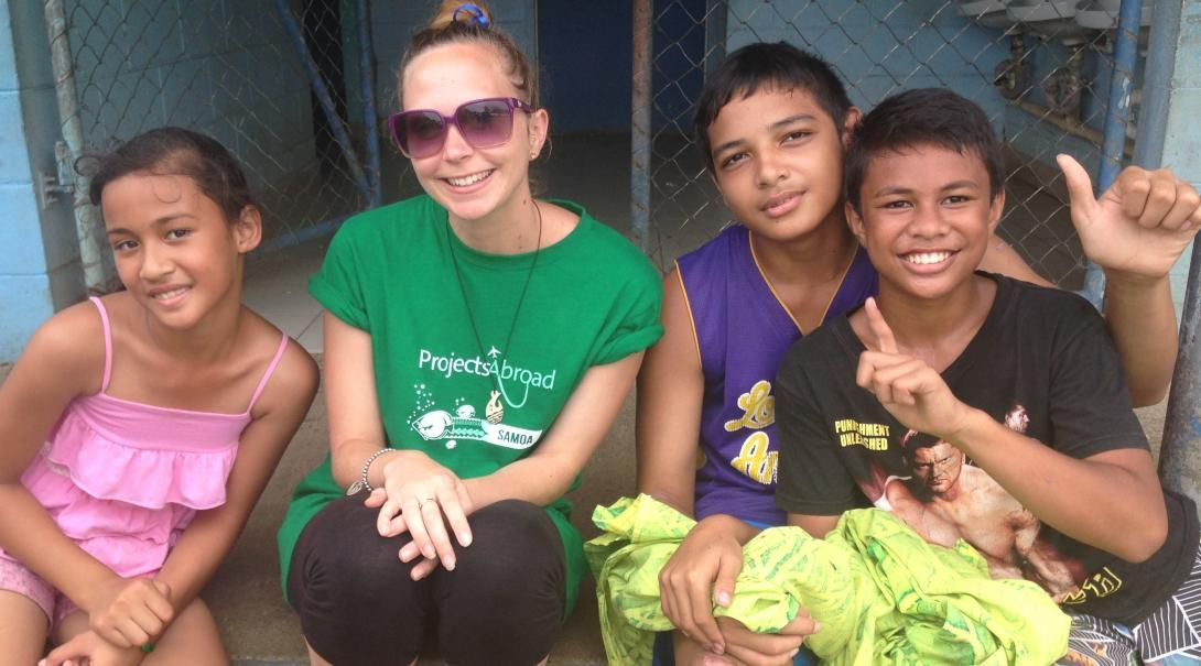A volunteer takes a picture with children in Samoa on her trip teenagers
